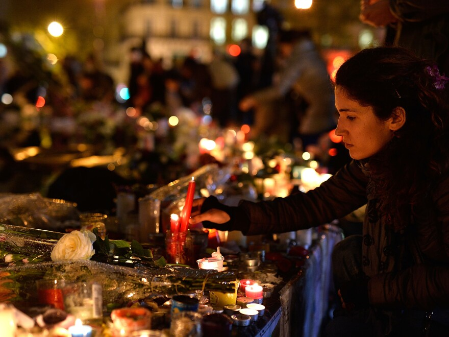 A woman lights a candle at the Place de la Republique in Paris on Friday, marking a week since the terrorist attacks.