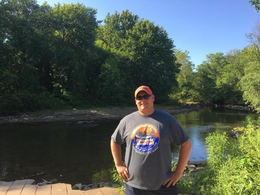 Brad McBride, of Burning River Adventures, stands near the banks of the Cuyahoga River. (Elizabeth Miller/WCPN)