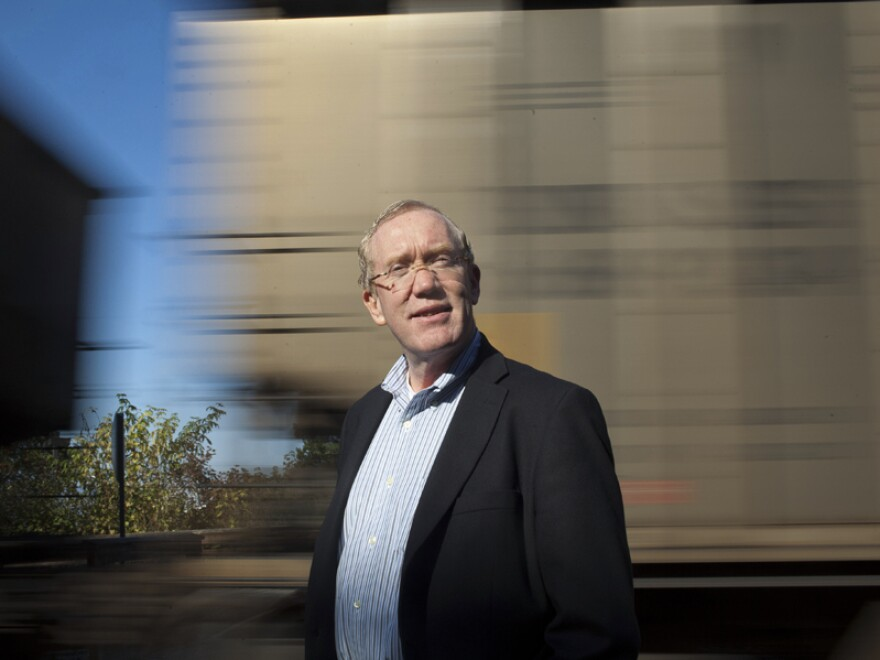 <p>Bellingham Mayor Dan Pike stands in front of a passing coal train at one of the major parks in downtown Bellingham. The proposed coal port is a big issue politically, and Pike is fully opposed to the port development.</p>