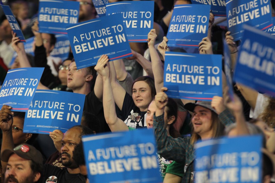 Supporters hold signs and cheer as Democratic Presidential candidate Bernie Sanders takes the stageduring a campaign stop in St. Charles, Missouri on March 14, 2016.