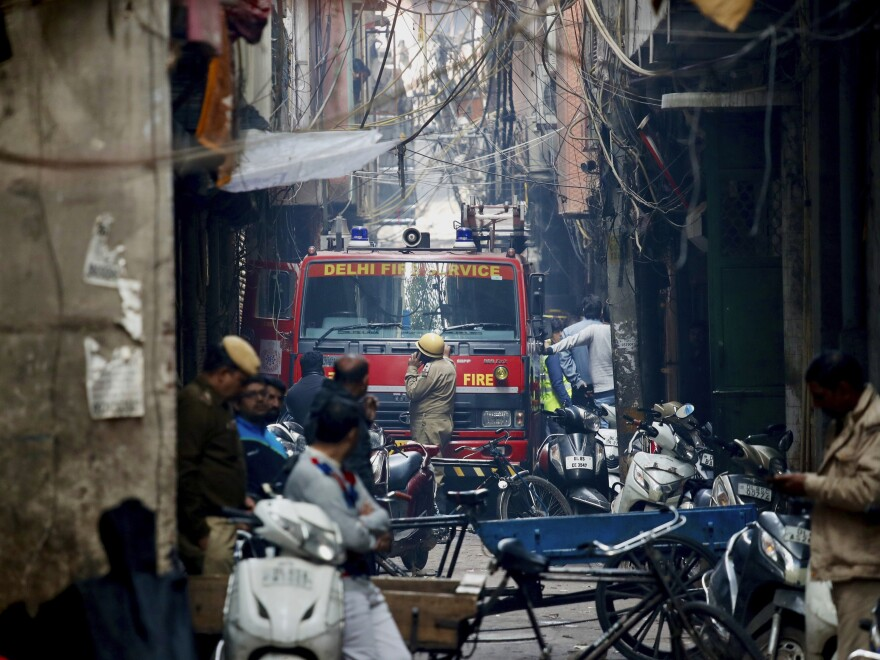 A fire engine stands by the site of the fire in an alleyway, tangled in electrical wire and too narrow for vehicles to access.