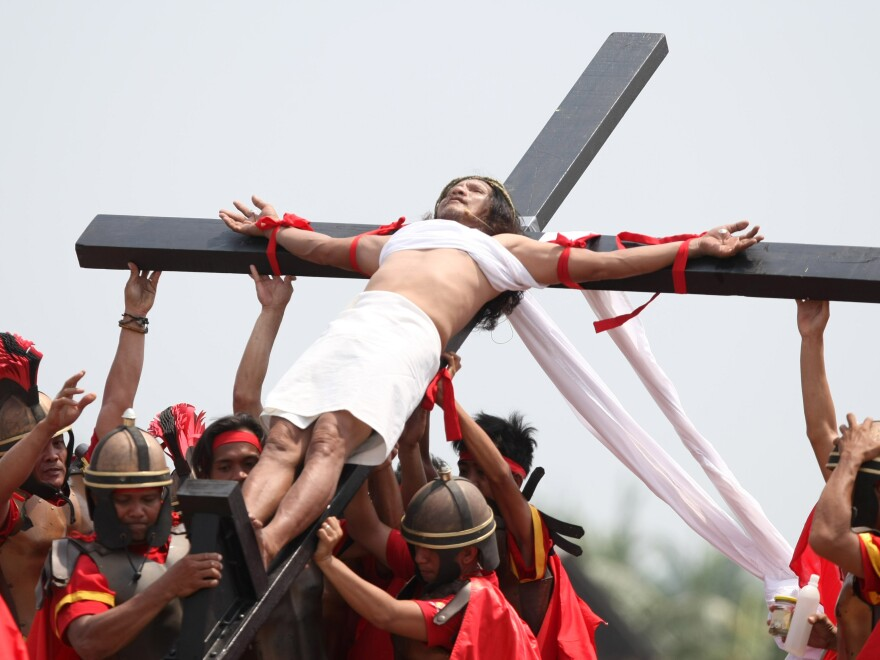 Ruben Enaje is hoisted by volunteers after he was nailed to a wooden cross in a reenactment during Good Friday rituals in the northern Philippines.