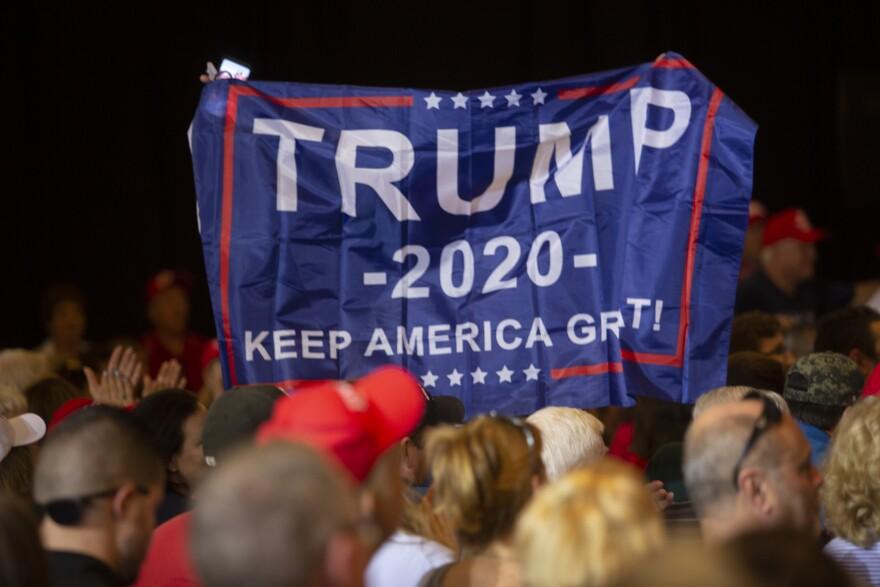 Holding a Trump 2020 banner aloft