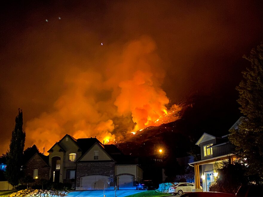 Photo of flames and smoke burning on a hill behind houses.