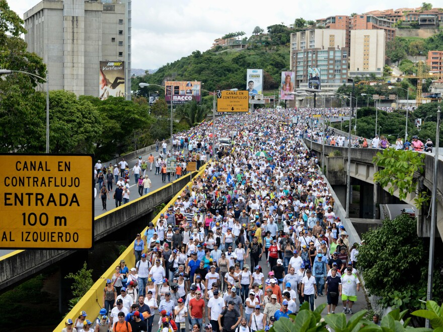 A crash in oil prices and political instability under President Nicolas Maduro has led to food shortages. And that has prompted almost daily street protests by thousands of Venezuelans. Here opposition activists march on the Francisco Fajardo Highway in Caracas on June 19.