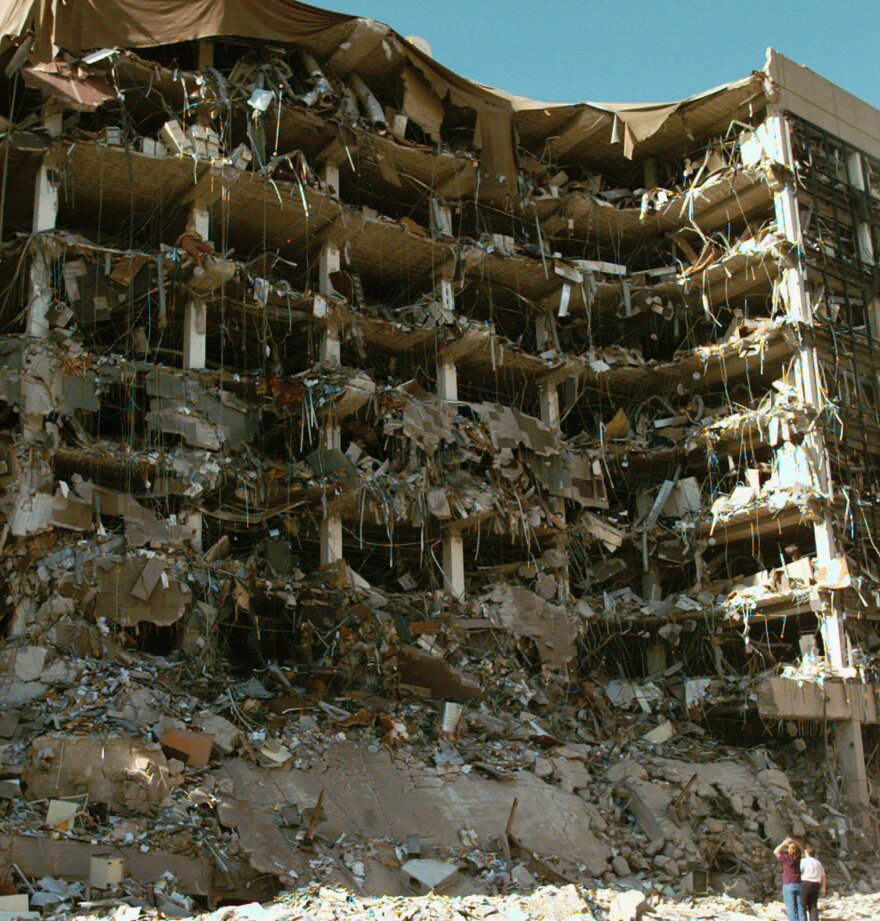 Rescue workers stand in front of the Alfred P. Murrah Federal Building in Oklahoma City after an explosion on April 19, 1995. The bombing killed 168 people.