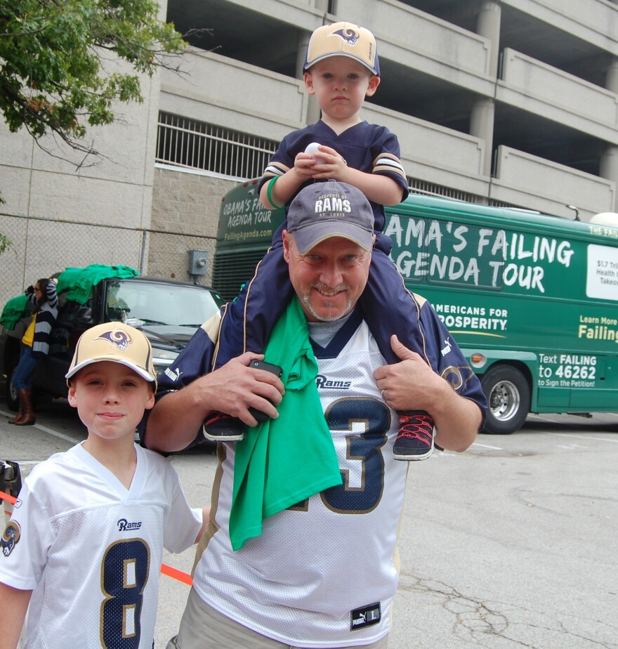 """Rowdy Smith, who brought his sons to the St. Louis Rams game on Sunday, said that President Obama's """"not a leader"""" and is hurting the energy industry. He's shown here walking in front of the Americans for Prosperity campaign bus."""