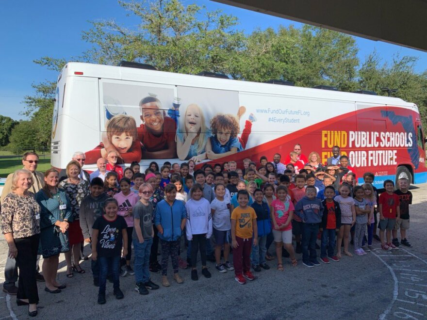 Elementary school students pose by the 'Fund Our Future' bus.