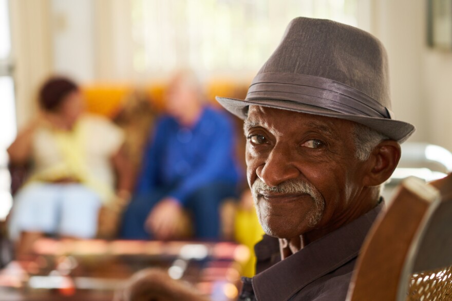 A Black senior is sitting in a retirement home with friends in the background.