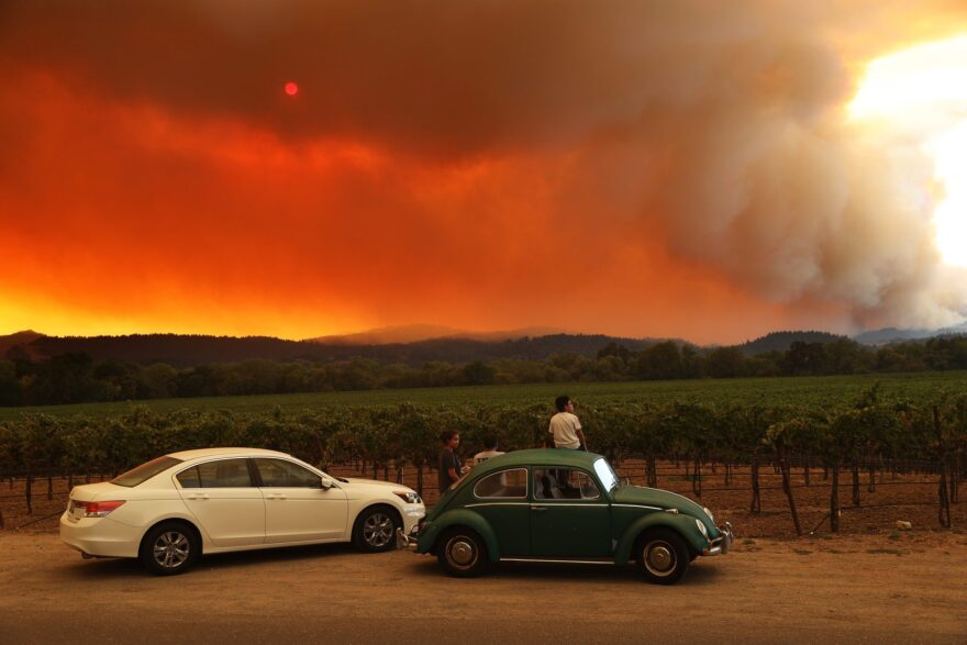 Local residents sit next to a vineyard as they watch the LNU Lightning Complex fire burning in nearby hills in Healdsburg, California.