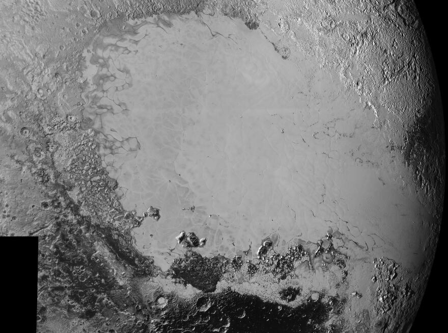 "This image, which shows the surface variety on Pluto, is ""dominated by the informally-named icy plain Sputnik Planum, the smooth, bright region across the center."""