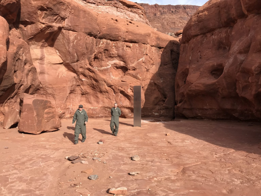 A photo of two men in green suits next to the silver-colored monolith.