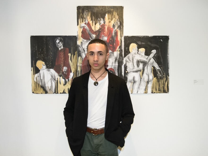 Juniel Solis poses in front of his work.