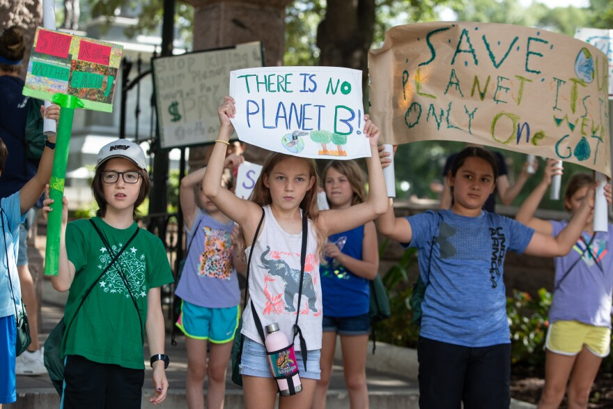 Parkside students Levi King, Savvy Horne-Lalande and Gabriel Guerrero hold signs demanding action on climate change.