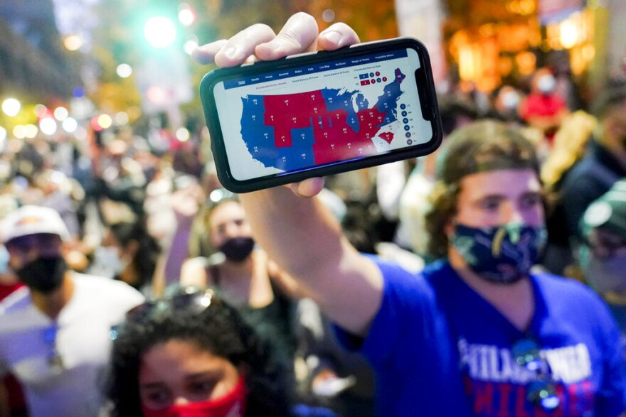 A supporter of President-elect Joe Biden holds up his mobile phone to display the electoral college map outside the Philadelphia Convention Center after the 2020 Presidential Election is called, Saturday, Nov. 7, 2020, in Philadelphia. (John Minchillo/AP Photo)