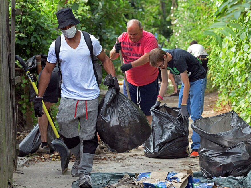 Volunteers clear an alley strewn with trash near Fulton Avenue in Baltimore on Aug. 5. Another group was in the city Thursday doing similar cleanup.