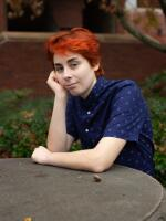 Person with red & orange hair sitting down at a stone table.