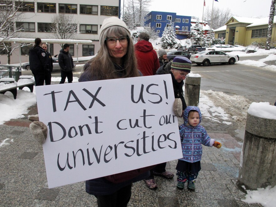 Luann McVey holds a sign before the start of a rally held in support of the Alaska university system on Feb. 13 in Juneau, Alaska.