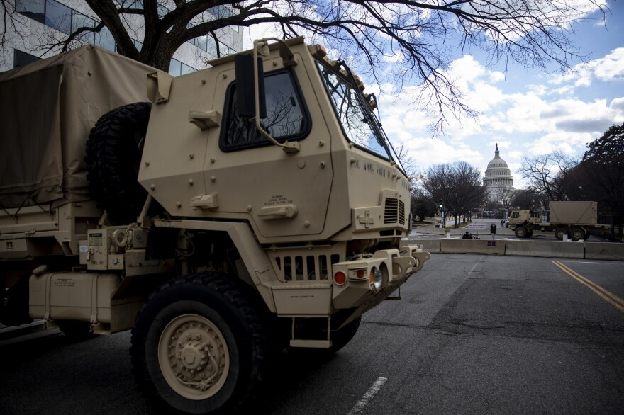 Military vehicles and concrete dividers block streets as part of the security perimeter near the U.S. Capitol.