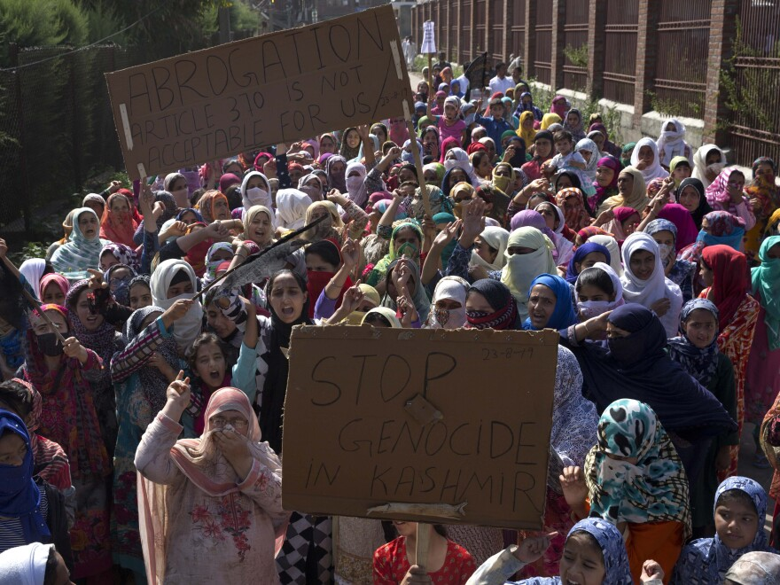 Kashmiri women hold placards and shout pro-freedom slogans during a protest after Friday prayers on the outskirts of Srinagar on Aug. 23.