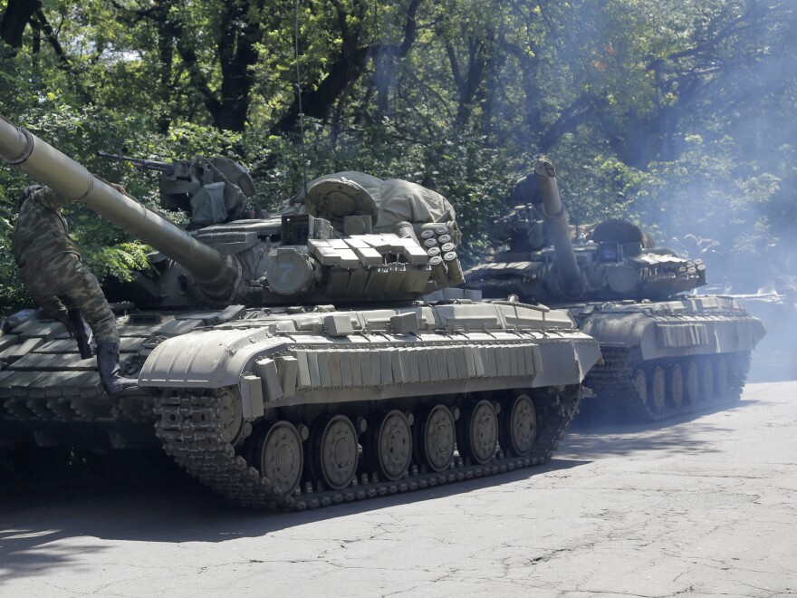 Pro-Russian troops prepare to travel in a tank on a road near the town of Yanakiyevo, Donetsk region, eastern Ukraine, on Friday. Ukraine's president has called a unilateral weeklong cease-fire.