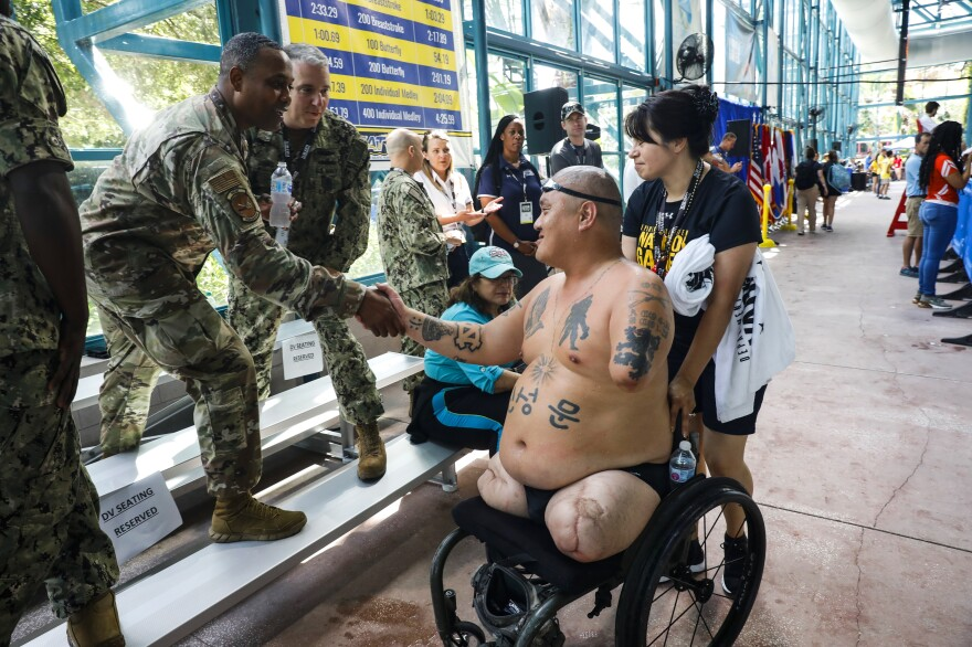 "Matt shakes hands with members of the Warrior Games community after his race. ""I got a letter saying that I was out of the [caregivers] program because the veteran hasn't shown any progress since 2011,"" Alicia said. ""I asked them, 'What do you mean by progress?' """
