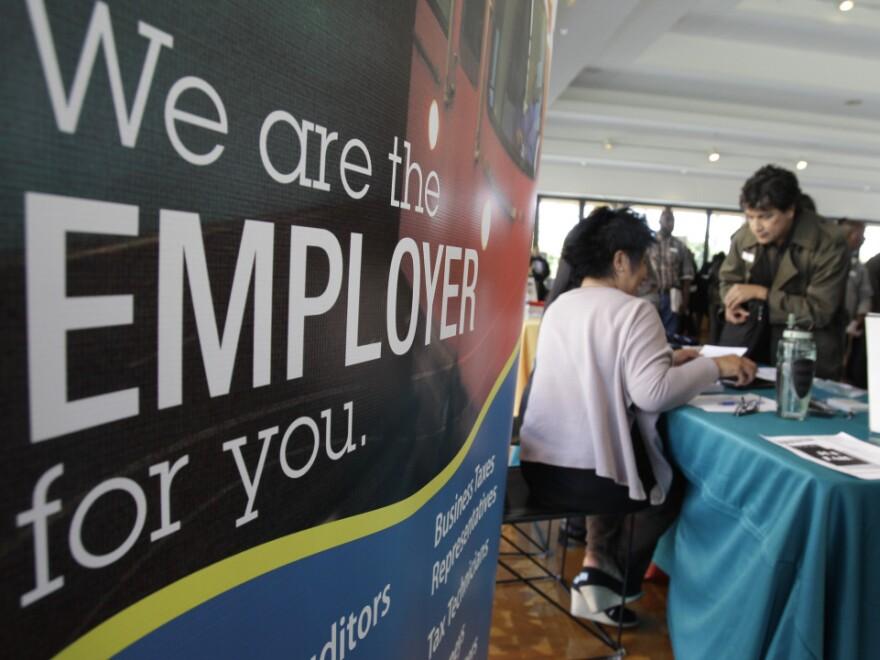 A job applicant listens to a recruiter at a job fair in San Jose, Calif.
