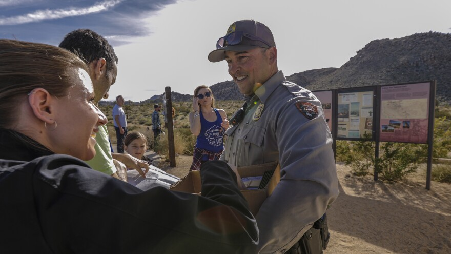 Lone park ranger Dylan Moe provides maps to visitors at the entrance to Joshua Tree National Park last Saturday, the first day of the government shutdown.