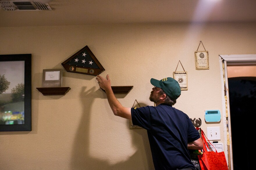 Davidson adjusts an award that hangs on the wall at his home in San Antonio, Texas.