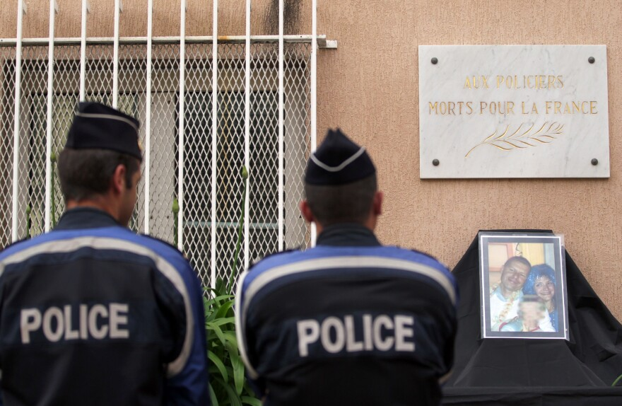 Police officers stand in front of a photo showing a French policeman and his partner, who were killed on June 13 by a man claiming allegiance to the Islamic State group.