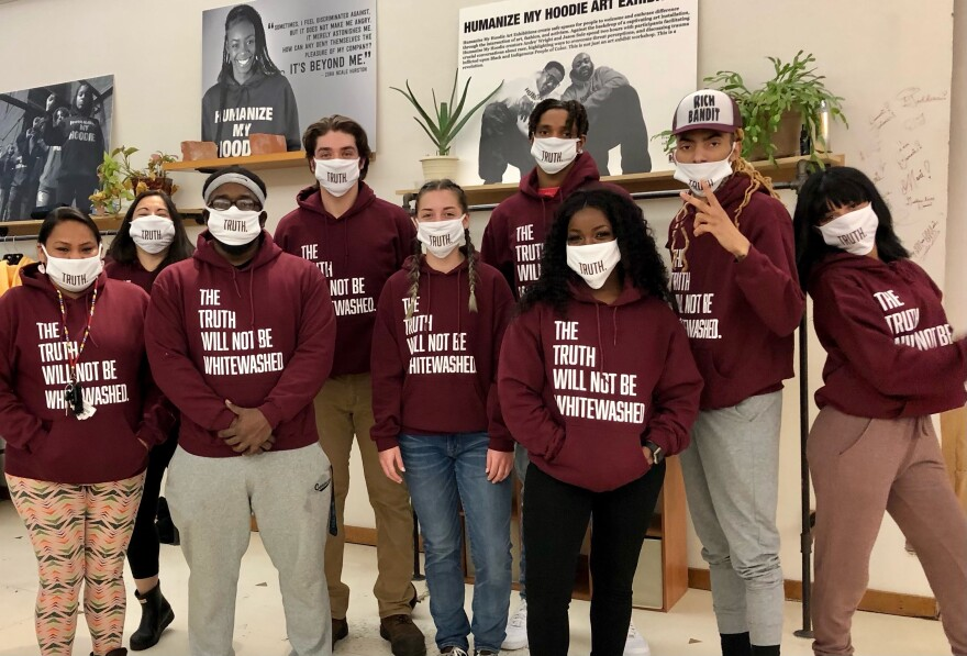 """A group of people pose for a photo. They are wearing maroon sweatshirts that say """"The truth will not be whitewashed,"""" and matching masks."""