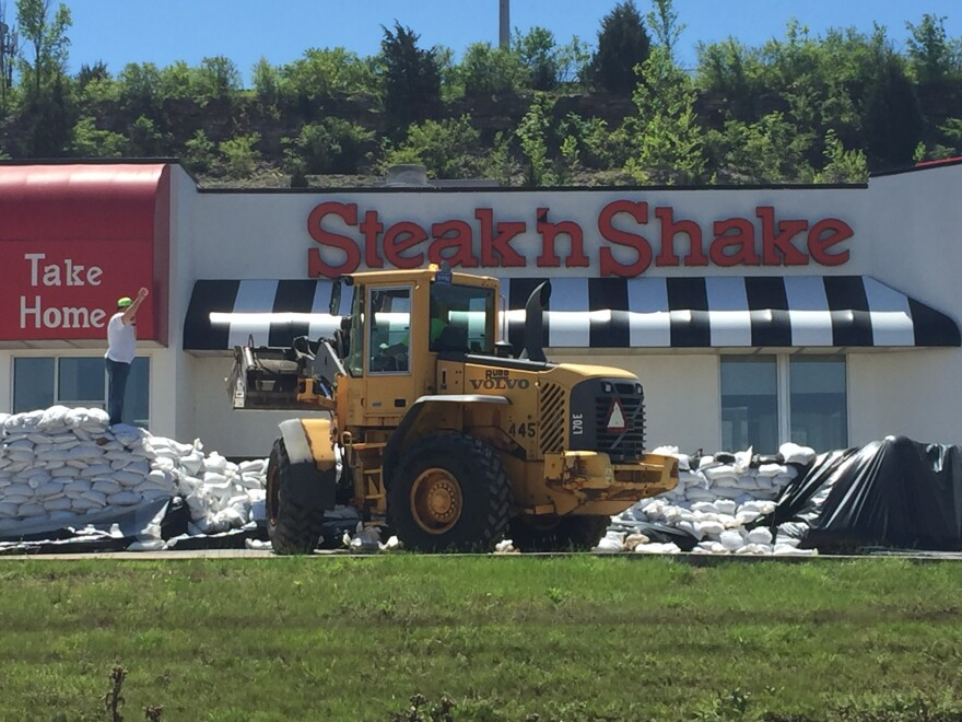 Crews remove hundreds of sandbags Sunday morning at the Steak 'n Shake in Valley Park. The city's mayor tells St. Louis Public Radio the sand wall at the fastfood restaurant near I-44 and Route 141 did not hold during last week's flood.