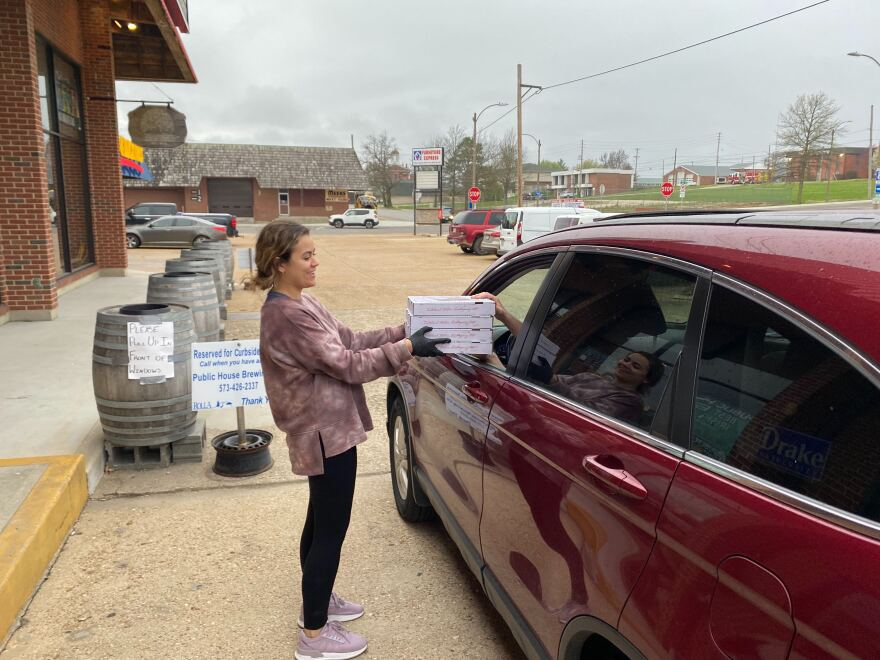 A Public House Brewing Company employee brings pizza to a curbside customer. It's a small business trying to make it in a collge town where the students have largely left town. 4-02-20