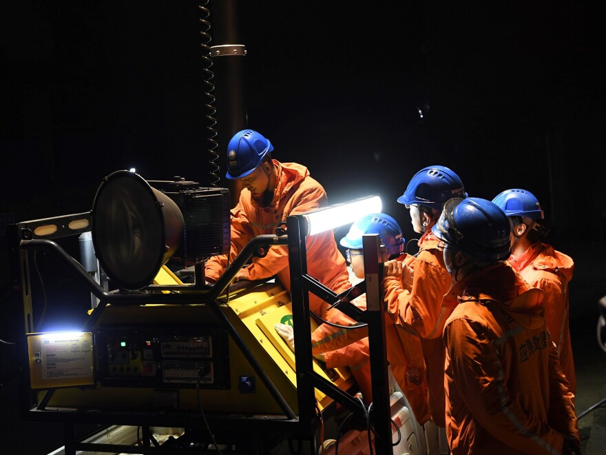 Rescuers adjust an emergency generator at the Diaoshuidong coal mine in southwest China on Saturday after a carbon monoxide leak at the facility left 18 dead. Rescue efforts were underway to reach five others still trapped underground.