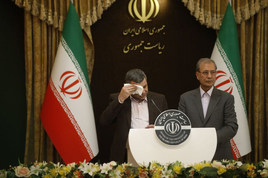 Iranian Deputy Health Minister Iraj Harirchi (left) wipes the sweat off his face, during a news conference with government spokesman Ali Rabiei in Tehran on Feb. 23. The next day, Harirchi confirmed he tested positive for the novel coronavirus.