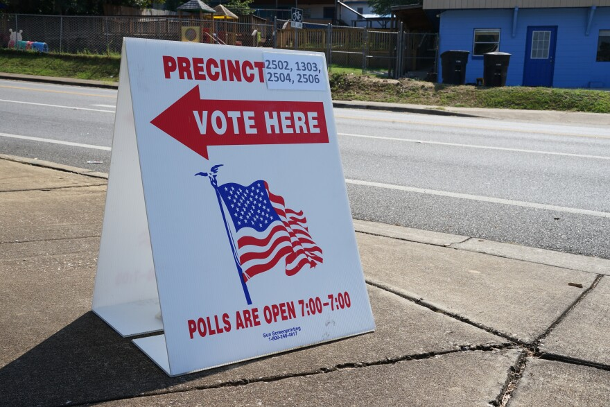 """A sign is placed on a sidewalk corner. It reads, """"Precinct 2502, 1303, 2504, 2506."""" Below those words is a big arrow pointing to the left. """"Vote here,"""" is written on the arrow. Below is an illustration of an American flag. Below the flag are the words, """"Polls are open 7:00 - 7:00."""""""