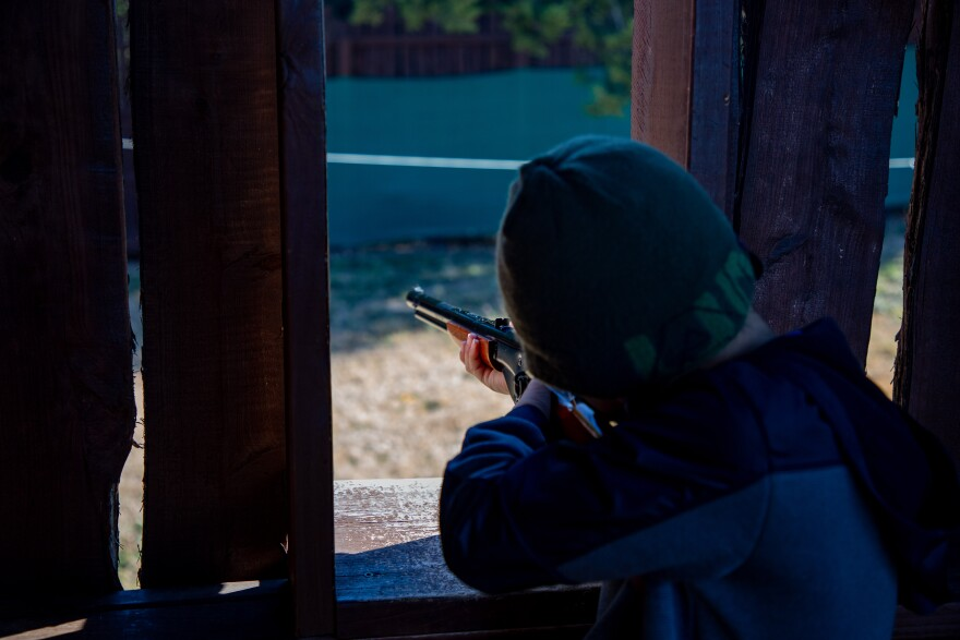 A little boy aims a BB gun.