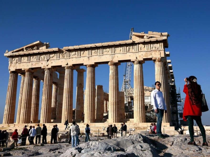 Tourists take pictures in front of the Parthenon Temple in Athens. If Greece leaves the eurozone, it could revert to its own currency, and the price of visiting the country could potentially drop.