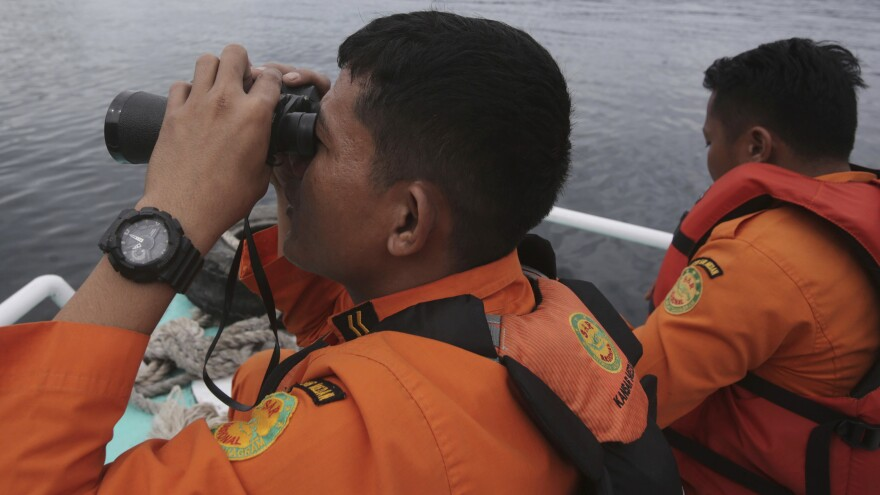 Indonesian rescuers scan the horizon from the deck of a rescue ship as they search for a ferry which sank in Lake Toba, North Sumatra, Indonesia on Monday.