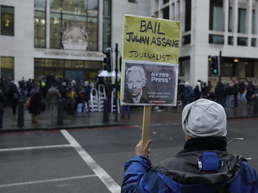 A Julian Assange supporter holds up a placard outside Westminster Magistrates Court, the site of his bail hearing, in London on Wednesday.