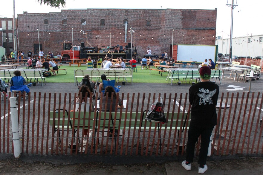 A man stands outside and gazes into a fenced-in outdoor music room with picnic tables, a DJ booth, a projection screen, and a flatbed truck converted to a stage.