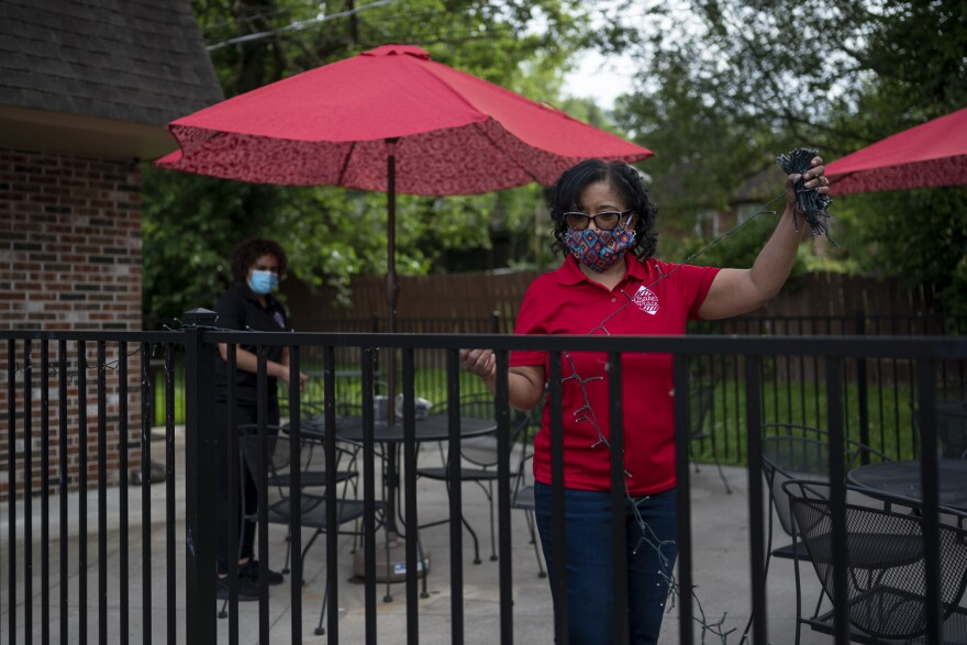 Drake's Place restaurant co-owner Bridgett Lewis strings lights around the restaurant's patio to attract customers to eat outside.  may 27, 2020