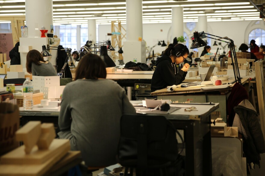 Architecture students work in a massive room with hundreds of drafting tables in the Foundation Building at Cooper Union.