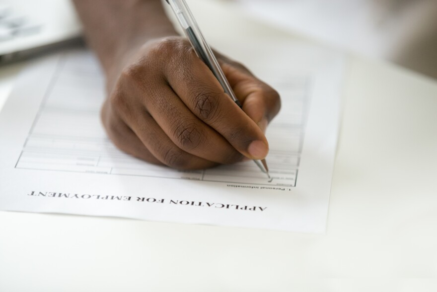 African-American man filling out an employment application. Close up view of his hand.