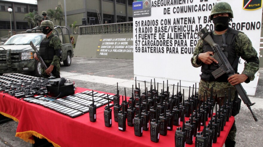 Mexican soldiers stand guard behind communication radios seized from alleged drug cartel members in Veracruz, Mexico, Nov. 23.