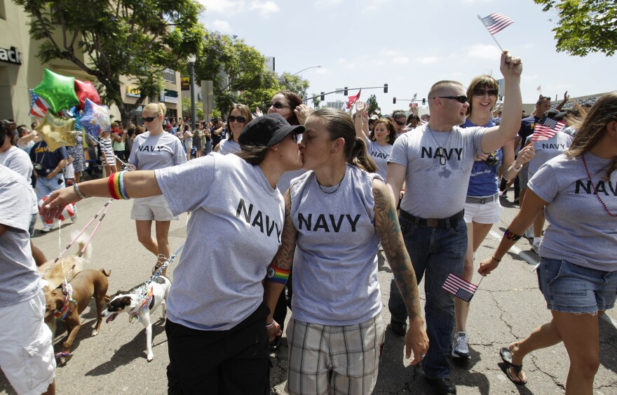 In this July 16, 2011 photo, two women, both active duty sailors in the Navy who gave their names as Nikki, left, and Lisa, kiss as they march in the Gay Pride Parade in San Diego.