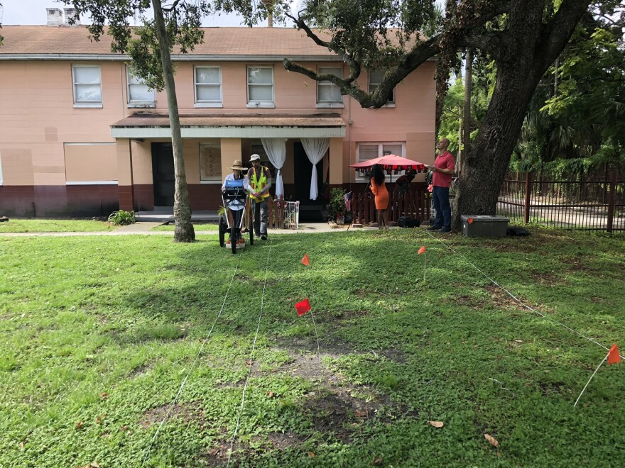 Researchers work with ground-penetrating radar in a housing complex yard
