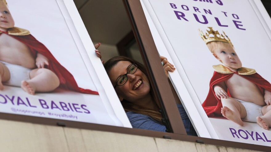 """A worker of a games company poses with placards depicting a """"royal baby"""" near the St. Mary's Hospital Lindo Wing in London on Thursday. While Buckingham Palace has been mum on the subject, Saturday was rumored to be the official due date for the child who will become the third in line to the British throne."""