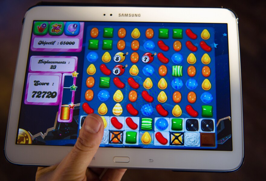 A person plays Candy Crush Saga on his tablet in Lille, northern France. This year, mobile games revenues are expected to fly past console games and hit more than $30 billion worldwide.