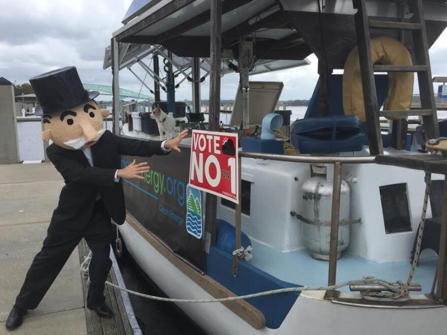 An activist with the Southern Alliance for Clean Energy poses as the Monopoly man next to the Archimedes in Jacksonville.